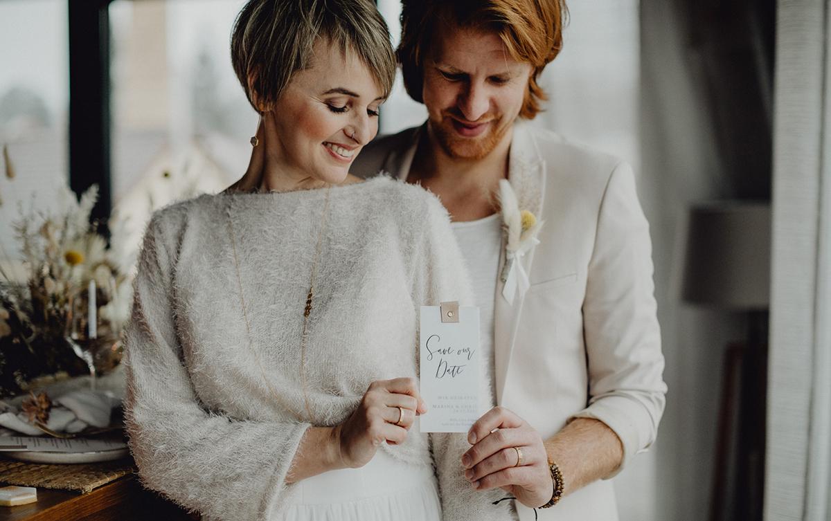 Brautpaar mit Save the Date Karte in der Hand